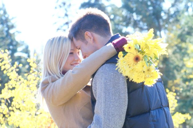 teenagers outside embracing couple flowers winter nature tenderness bunch